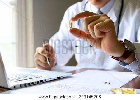 doctor working on a computer at his cabinet and shows a pill to patient