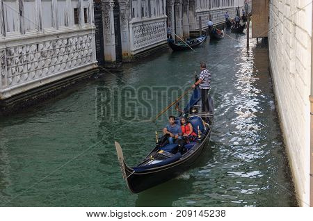 VENICE ITALY - SEPTEMBER 29 2017: Canal in Venice with gondolas and gondoliers old houses in Venice Italy