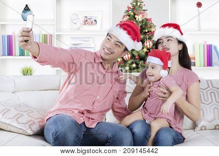 Picture of Asian family wearing Santa Claus hat while taking a selfie picture with a smartphone. Shot at home