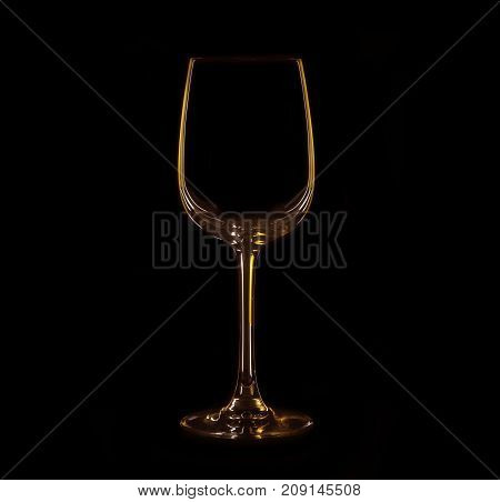 Silhouette of wineglass isolated on black with yellow and brown illumination