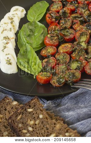 Cherry tomatoes baked in the oven with basil and mozzarella