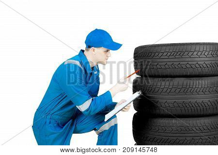 Image of an American male mechanic squatting in the studio while checking tires and holding a clipboard