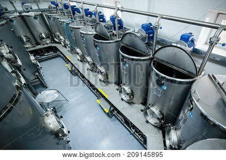 A lot of stainless steel tanks with large round hatches, modern beverage production. Food industry.