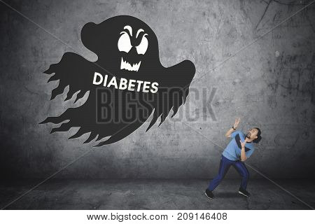 Picture of a scared Afro man wearing sportswear while looking at a ghost with diabetes word