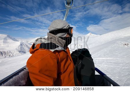Close-up of skier on cable car and snow ski at sun winter day. Caucasus Mountains Georgia region Gudauri.