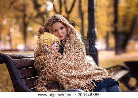 cute little boy with her mother walking in the autumn in the park in the yellow foliage and sitting in a rug