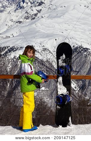 Young snowboarder with helmet in hands and snowboard on viewpoint in winter mountains at sun day. Caucasus Mountains. Hatsvali Svaneti region of Georgia.