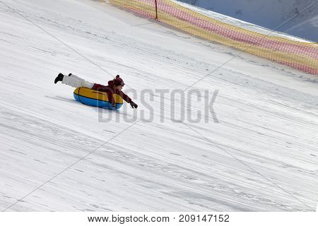 Happy girl downhill on snow tube on ski resort at sun winter day