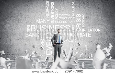 Confident businessman in suit standing on pile of documents among flying papers with business related terms on background. Mixed media.