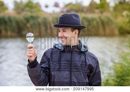 Men holding Light Bulb Electric on nature background, idea concept