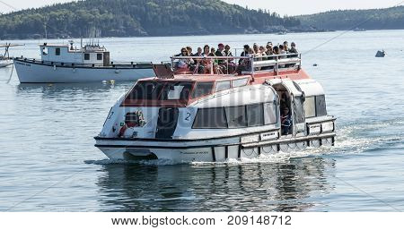 Bar Harbor Maine USA - 31 July 2017: A cruise ship tender arriving in Bar Harbor Maine with passengers riding inside and on top of it for a day of visiting and shopping.
