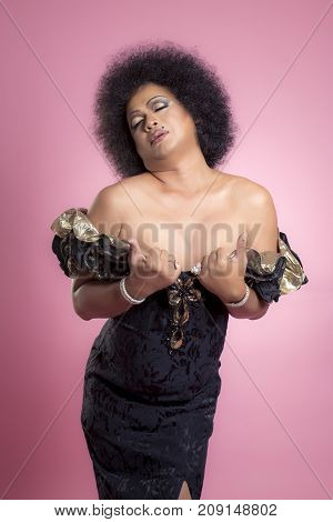 Fat man makeup his face and wear women dress on pink background.(Drag queen fashion concept)