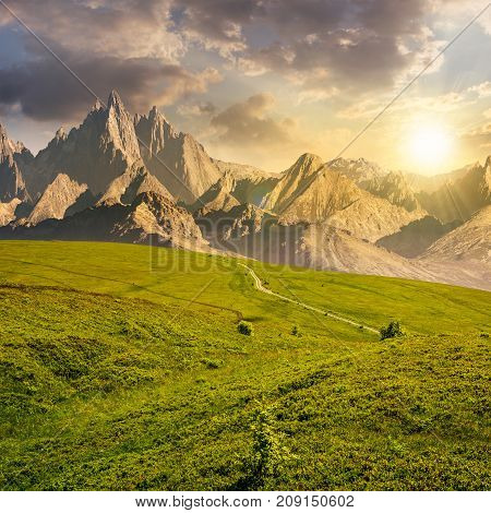 grassy slopes and rocky peaks composite. gorgeous summer landscape with magnificent mountain ridge over the pleasing green meadows. lovely surreal fantasy scenery at sunset