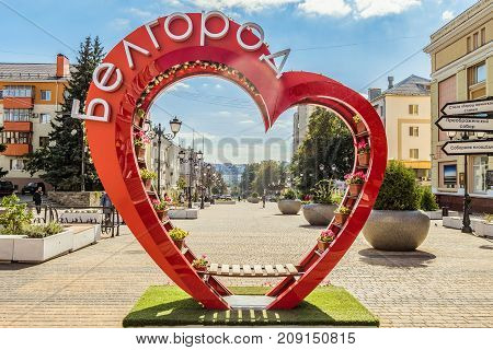Belgorod Russia - September 29 2017: Street of the fiftieth anniversary of the Belgorod region. Pedestrian street in the old residential center of the city. City environment. Bench of love in the shape of a heart with flower pots.