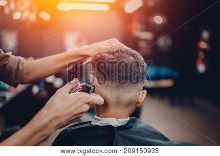 Barber shop. Close-up of a master shearing a man. shaves pattern on hair