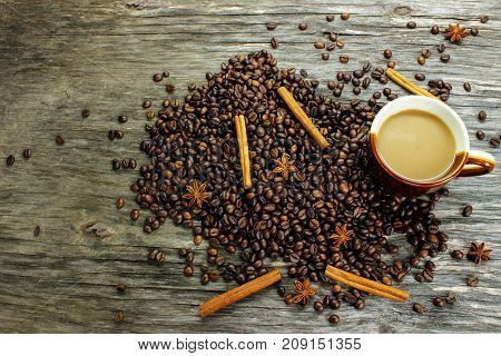 A cup of coffee and coffee beans anise and cinnamon on a wooden table. view from above