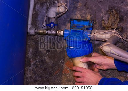 the plumber installs a water filter in the cellar located