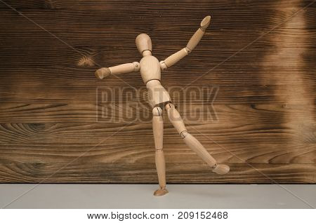 Simple happy dancing wooden man on wooden surface background. Happy lifestyle. Good day.