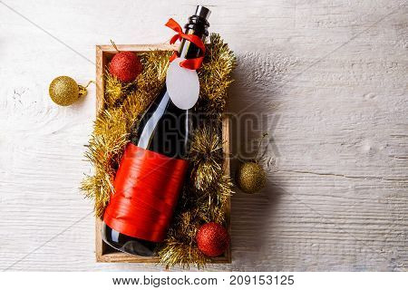 Image of bottle of wine with blank card in box with tinsel, Christmas balls on white table