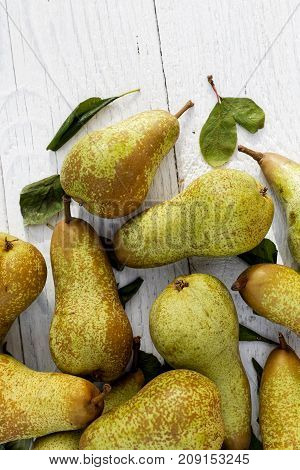 Abate fetel pears with leaves on white painted wood from above. Space for text. poster