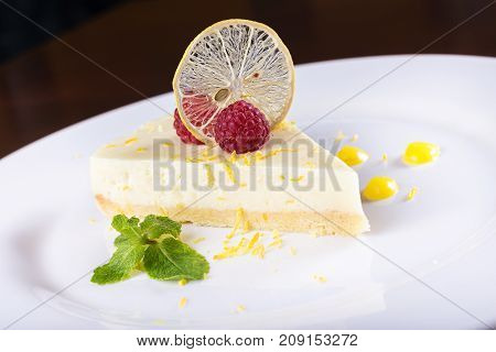piece French lemon tart garnished with fresh raspberries mint and slice of lemon