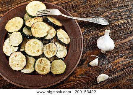 Fried slices of zucchini vegetarian meal on a wooden table. Close are whole zucchini garlic and fork