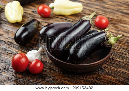 Vegetables on vintage wood background - summer harvest soup ingredients. Rural still life from above. Tomato eggplant garlic pepper