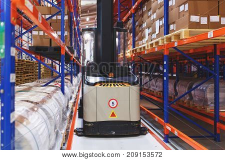 System of address storage of products, materials and goods in a warehouse. Managed electric forklift between rows. Modern warehouse and storage systems.