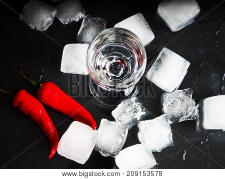 A Shot Of Vodka, An Alcoholic Beverage, Next To Ice, Fire, Ice, Red Chili Pepper. The Concept Of Alc