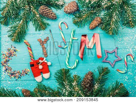 Toned photo of blue table with spruce branches, word Christmas from sweets, Bengal fire, sparkles, Santa clothes