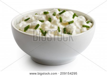 White Ceramic Bowl Of Chunky Cottage Cheese Garnished With Chives Isolated On White.