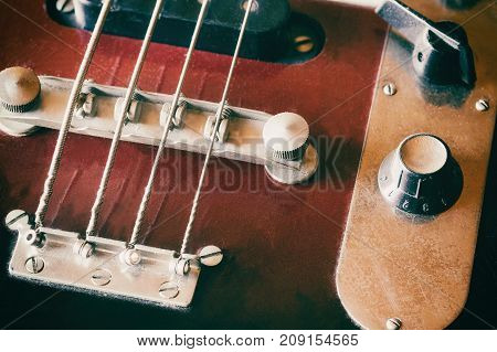 Used electric bass guitar closeup. Edited as a vintage photo with dark edges. All potential trademarks are removed.