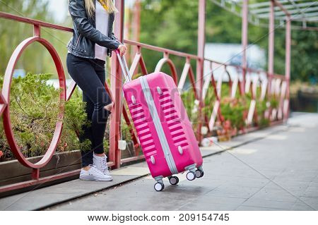 A beautiful girl stands at a railing with a pink suitcase waiting for her route