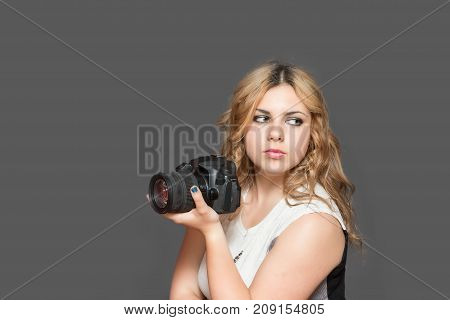 Portrait of serious attractive long haired young woman holding a camera. All potential trademarks are removed. All is on the gray background.