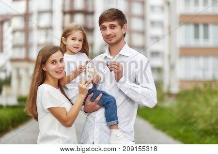 Lovely young family holding keys to their new apartment smiling joyfully posing outdoors. Husband and wife with their child holding keys to new house family happiness love concept