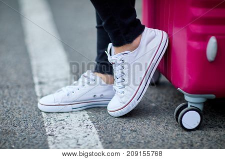 A young, pretty girl with a pink suitcase standing on the street legs, sneakers and a suitcase close-up