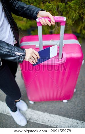 A young, beautiful girl with a pink suitcase standing on the street feet, sneakers and a suitcase close-up with a ticket