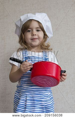 Portrait cute smiling chef cook girl enters the frame and standing at the kitchen