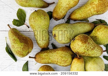 Abate fetel pears with leaves on white painted wood from above. poster