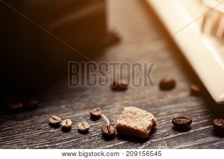 Coffee shop vintage color. Coffee grinder and Brown cane sugar on wooden table with flare blurred background. Retro style image. Glare of light.