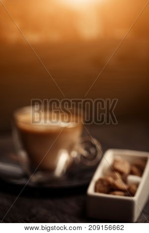 Blurred background of cup of coffee in coffee shop. Vintage color. Brown cane sugar on wooden table. Retro style image. Glare of light.