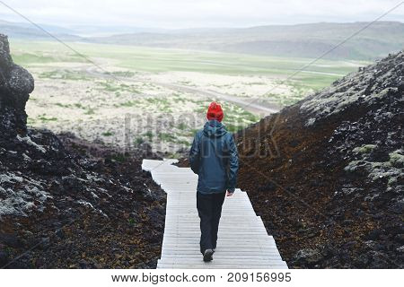 Girl in warm clothing walks in crater of volcano on background of mountains of Iceland.