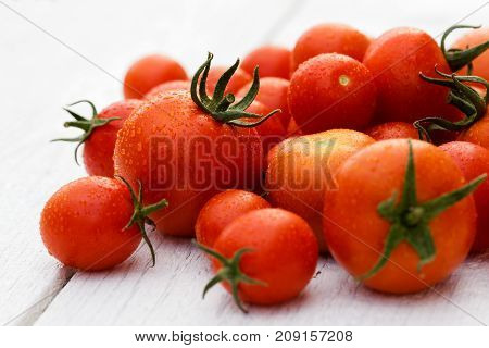Mixed Wet Large And Small Tomatoes With Stalks On White Wood Board.
