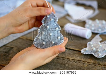 Small child shows a Christmas toy. Child holds a Christmas toy in his hands. Child sewed a Christmas tree ornament from felt. Winter art project for kids all age