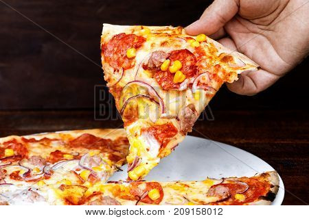 Man's Hand Holding A Slice Of Salami And Sweetcorn Pizza. Brown Background.