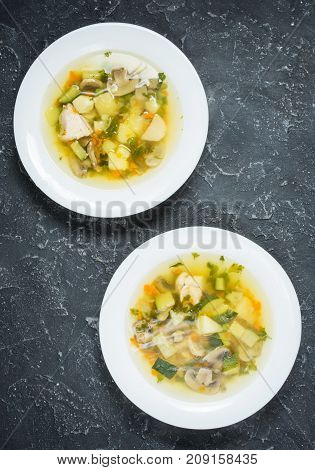 Soup with Mushrooms and chicken on stone background top view.