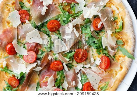 Detail Of Prosciutto Pizza With Cherry Tomatoes And Rucola From Above.