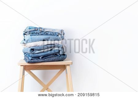 jeans denim cloth garment monochrome gray blue linen textile stacked on wooden chair near white wall pile concept