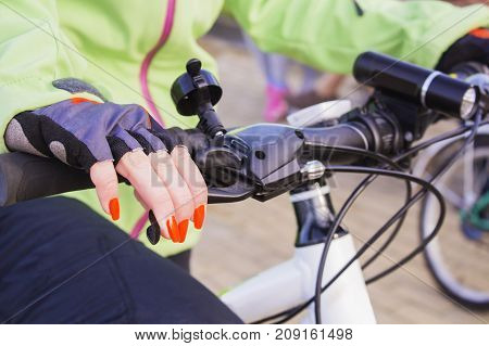 Woman's hand with bright nail Polish on the Bicycle wheel. A healthy way of life.