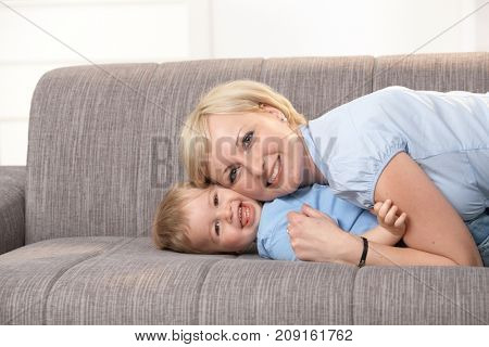 Happy young mother and baby boy having fun together on sofa.